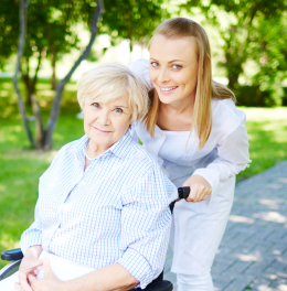 caregiver and old woman roaming around at the park