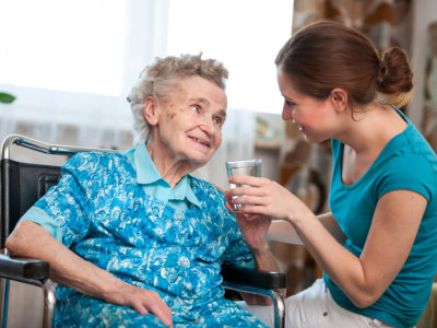 Caregiver giving glass of water to the elderly woman